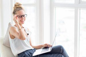 Smiling Woman Working on Laptop at Windows - Career Confidence